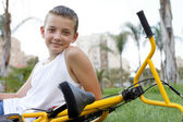 Boy with a bicycle sitting — Stock Photo