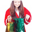 Pretty teen girl dressed as Santlooks gifts — Stockfoto #15434837