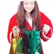 Stock Photo: Pretty teen girl dressed as Santlooks gifts