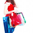 Cute long-legged girl as Santa with shopping — Stock Photo