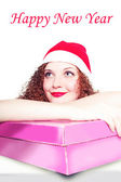 Portrait of curly girl as Santa with a gift — Stock Photo