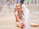 Cute girl enjoying the fountains on a hot day — Stock Photo