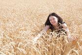 Chica guapa se baña en un campo de trigo — Foto de Stock