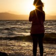 Silhouette of a girl at the beach at sunset — Stock Photo