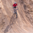 Rider on bike, with steep hill — Stock Photo #37323583