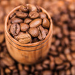 Fresh aromatic coffee beans in a wooden cup — Stock Photo