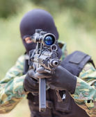 Soldier with a gun sighting optics — Stock Photo