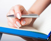 Female hand with pen and notebook — Stock Photo