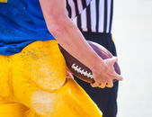Are referees and player holding the ball in his hands — Stock Photo