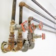 Stock Photo: Old Plumbing Pipes with Valves on Wall
