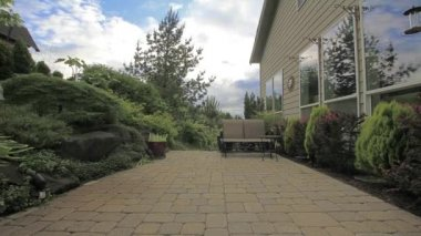 Backyard Concrete Paver Patio with trees, plants, glider, potted plant, moving white clouds and blue sky window reflection timelapse — Stock Video