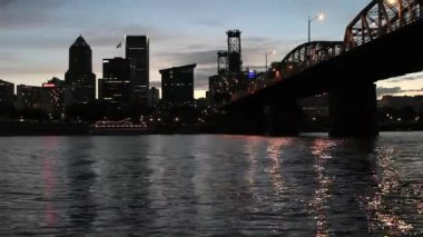 Portland Oregon Downtown City Skyline along Willamette River with Hawthorne Bridge and Water Reflection Dancing Lights at Sunset Dusk 1920x1080 — Stock Video