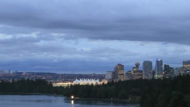 View of Vancouver BC Canada City Skyline with Moving Clouds and Traffic along Stanley Park Seawall from Lions Gate Bridge at Blue Hour into Night Time Lapse 1080p — Stock Video