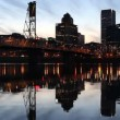 Stock Video: Portland Oregon Scenic View of Downtown City Skyline with Hawthorne Bridge across Willamette River Beautiful Water Reflection at Blue Hour 1080p