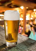 Glass of beer in pub — Stock Photo