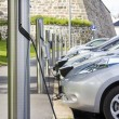 Electric car plugged in to electricity — Stock Photo