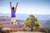 Young woman joyfully jumping in Bryce Canyon Park — Stock Photo