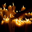Human hand lighting candle in church - Stock Photo