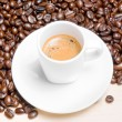 Detail of white cup with espresso coffee near coffee beans — Stock Photo