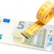 Stock Photo: Roll of measuring tape on new five euro banknote