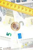 Money euro coin on banknotes near measure tape — Stock Photo