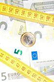 монета евро на банкнотах вблизи ленты мера — Стоковое фото