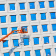 Worker cleaning high tower — Stock Photo