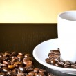 White cup with coffee near coffee beans — Stock Photo
