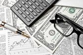 Detail of dollars near glasses, calculator and golden pen — Stock Photo
