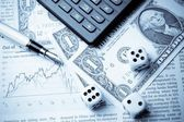 Dice on financial chart near dollars and calculator — Stock Photo
