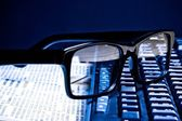 Glasses on financial newspaper — Stock Photo
