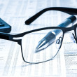 Glasses near calculator with pen on financial newspaper — Stock Photo