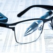 Glasses near calculator with pen on financial newspaper — Stock Photo #32355695
