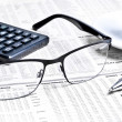Detail of a pen and glasses near a calculator with cup of coffee  — Stock Photo