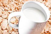Cup of milk on corn flakes — Stock fotografie