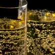 A pair of flutes of champagne tilted with golden bubbles — Stock Photo #34769959