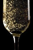 Flute of champagne with golden bubbles — Stock Photo