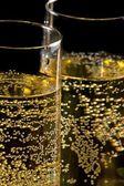 Een paar van fluiten van champagne gekanteld met gouden bubbels — Stockfoto