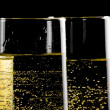 Detail of a pair of flutes of champagne with golden bubbles — Stock Photo