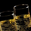 Stock Photo: A pair of flutes of champagne with golden bubbles