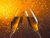 Pair of a champagne flutes on golden light bokeh background — Stockfoto