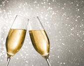 Champagne flutes with golden bubbles on silver light bokeh background — Stock Photo