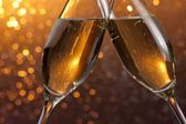 Detail of a champagne flutes with golden bubbles on orange light bokeh background — Stock Photo