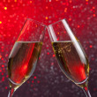Stock Photo: Pair of champagne flutes with gold bubbles on red and violet light bokeh background