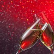 Stock Photo: Champagne flutes with gold bubbles on red and violet light bokeh background