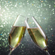 Champagne flutes with gold bubbles on green light bokeh background — Stock Photo