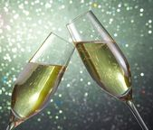 Champagne flutes on green light bokeh background — Stock Photo