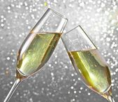 Champagne flutes on silver light bokeh background — Photo