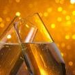 Two champagne flutes with gold bubbles on dark light bokeh background — Stock Photo