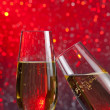 Two champagne flutes with gold bubbles on red light bokeh background — Stock Photo